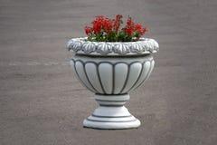 De decoratieve urn van de ijzertuin met roze bloemen stock afbeeldingen