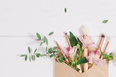 De decoratieve vlakte legt samenstelling met make-upproducten, kraftpapier-envelop en bloemen Vlak leg, hoogste mening over witte stock afbeeldingen