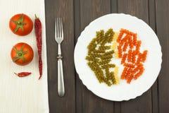 De Deegwaren van drie Kleurenrotini op een plaat Gekleurde deegwaren op de keukenlijst Reclame op deegwaren Stock Afbeeldingen