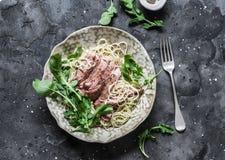 De deegwaren van het Pepperedlapje vlees Spaghettideegwaren met gesneden rundvleeslapje vlees en raketsalade op een donkere achte stock foto's
