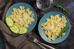 De deegwarenboog wordt bestrooid met kaas, rucolabladeren, verse komkommer, donkerblauwe achtergrond stock afbeelding