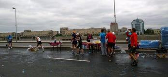 De deelnemers van de marathon` Witte Nachten ` bij één van de voedselpunten in het centrum van Petersburg royalty-vrije stock foto's