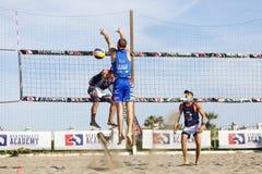 De defensie van het het strandvolleyball van de atletenmens Muur op het net Wapens omhoog Stock Foto