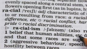 De definitie van het racismewoord in woordenboek, agressieve houding tegenover verschillende rassen stock videobeelden