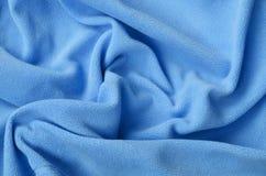 De deken van bont blauwe vachtstof Een achtergrond van het lichtblauwe zachte materiaal van de pluchevacht met heel wat hulpvouwe stock afbeeldingen