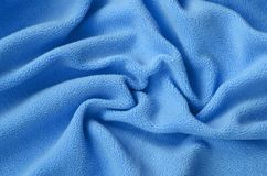 De deken van bont blauwe vachtstof Een achtergrond van het lichtblauwe zachte materiaal van de pluchevacht met heel wat hulpvouwe royalty-vrije stock afbeelding