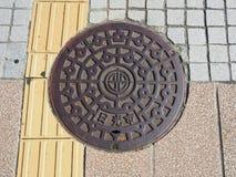 De dekking van het mangatafvoerkanaal op de straat in Nikko, Japan Stock Afbeelding
