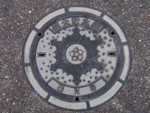 De dekking van het mangatafvoerkanaal op de straat in Nikko, Japan Stock Fotografie