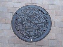 De dekking van het mangatafvoerkanaal op de straat in Osaka, Japan Royalty-vrije Stock Foto