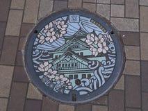 De dekking van het mangatafvoerkanaal op de straat in Osaka, Japan Stock Afbeeldingen