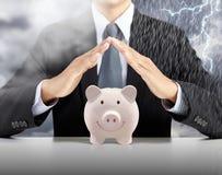 De dekkings roze piggy ceramische bank van de zakenmanhand met de achtergrond van het zware regenonweer stock afbeeldingen