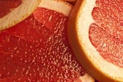 De delen van een rode grapefruit sluiten omhoog Stock Foto's