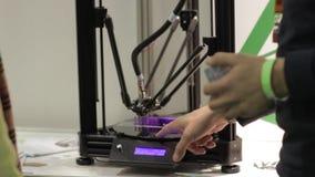 De delta 3D printer drukt productpurple een mens die met zijn handen en iets gesturing om te verklaren hoe het werkt stock video