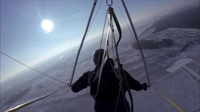 De deltavlieger vliegt in de zonnige hemel over de snow-covered weide stock video