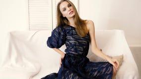 De demonstratie van nieuwe kleren, meisje bekijkt camera en stelt in kleding met lange benen op bank op fotospruit in studio stock videobeelden