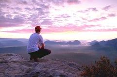 De denkende mens zit op rots Mens bij het blootgestelde top letten op stock afbeelding