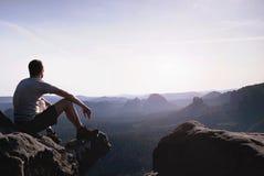 De denkende mens zit op rots Mens bij het blootgestelde top letten op royalty-vrije stock foto