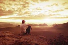 De denkende mens zit op rots Mens bij het blootgestelde top letten op royalty-vrije stock fotografie