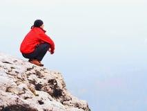 De denkende mens zit op rots Mens op meningspunt van het blootgestelde piek letten op aan nevelige verre afstand royalty-vrije stock fotografie