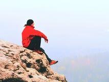 De denkende mens zit op rots Mens op meningspunt van het blootgestelde piek letten op aan nevelige verre afstand stock fotografie