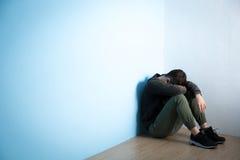 De depressiemens zit op vloer stock afbeelding