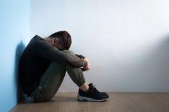 De depressiemens zit op vloer stock foto's
