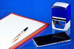 De Desktop van de bureauboekhouding, blauwe achtergrond, met de noodzakelijke toebehoren Omslag met documenten, smartphoneinforma stock afbeeldingen