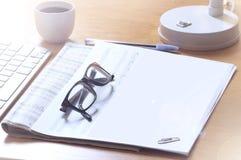 De Desktop van de effectenmakelaar terwijl het nemen van koffie het herzien effectenbeurzen in de krant royalty-vrije stock fotografie