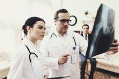 De deskundige chirurg en de verpleegster bestuderen dicht röntgenstraal van bekkenbeenderen van patiënt Ontvangst bij chirurg stock afbeelding