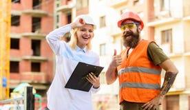 De deskundige en de bouwer communiceren over leveringsbouwmaterialen Aankoop van bouwmaterialen Bouwnijverheid stock afbeelding