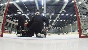 De deskundige keeper in zwarte verdedigt doel bij hockeygelijke stock footage