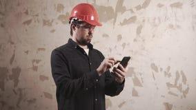 De deskundige werkman van reparatie berekent kosten van de werken in een ruimte met mobiel stock video