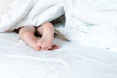 De dessous une couverture blanche, collez les pieds des enfants nus Copiez l'espace Photo lumineuse dans le lit photographie stock