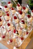 De details van een huwelijksdessert dienen - vanilleroom met verse rode frambozen in buitensporige glazen met lepels in royalty-vrije stock afbeeldingen