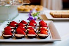 De details van huwelijk behandelt met witte room en aardbeien in chocoladekoppen stock foto's