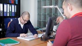 De detective in zijn bureau ondervraagt een slachtoffergetuige op het feit van misdadige aanval De werken van de agentschappen va stock footage