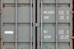 De deuren van een grote oude container zijn geschilderd in close-up in groen met roest, met pijp-type sloten en het witte het van stock foto