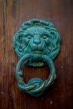 De deurkloppers van de koperleeuw op een houten deur Stock Foto