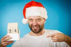 24 de dezembro O chapéu de Santa do homem guarda o calendário fotos de stock royalty free