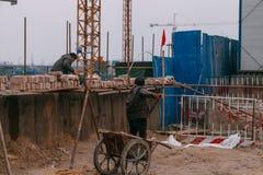 18 de dezembro de 2014 Pequim Dois homens em um canteiro de obras na cidade com guindastes e trabalhadores fotos de stock