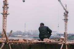 18 de dezembro de 2014 Pequim homens em um canteiro de obras na cidade com guindastes, == takeing dos tijolos fotos de stock