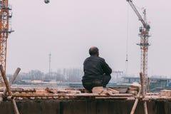 18 de dezembro de 2014 Pequim homens em um canteiro de obras na cidade com guindastes, a== takeing dos tijolos imagem de stock