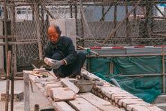 18 de dezembro de 2014 Pequim homens em um canteiro de obras na cidade com guindastes, tijolo takeing foto de stock royalty free