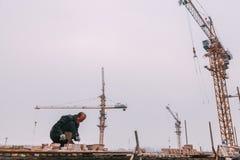 18 de dezembro de 2014 Pequim homens em um canteiro de obras na cidade com guindastes, tijolos takeing foto de stock