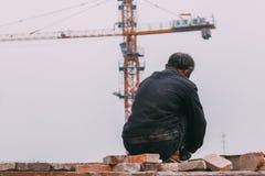 18 de dezembro de 2014 Pequim homens em um canteiro de obras na cidade com guindastes, tijolos takeing fotografia de stock royalty free