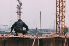 18 de dezembro de 2014 Pequim homens em um canteiro de obras na cidade com guindastes, tijolos takeing fotografia de stock