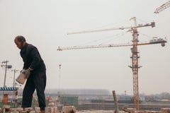 18 de dezembro de 2014 Pequim homens em um canteiro de obras na cidade com guindastes, tijolos takeing e imagem de stock