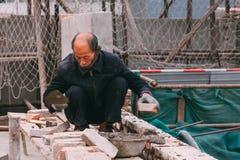 18 de dezembro de 2014 Pequim homens em um canteiro de obras na cidade com guindastes, tijolos takeing e fotos de stock royalty free