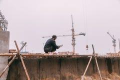 18 de dezembro de 2014 Pequim homens em um canteiro de obras na cidade com guindastes, tijolos takeing e imagem de stock royalty free