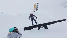 De dia van de cameramanspruit snowboarder op sleep bij helling Skitoevlucht in bergen uitdaging tekortkoming stock video